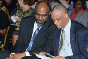 Senior Advisor to the Minister of Education, Radley Lewis (right) and General Manager of the Jamaica National Building Society (JNBS), Earl Jarrett, engage in conversation at an early childhood development conference at the Jamaica Pegasus Hotel in Kingston, on March 25.