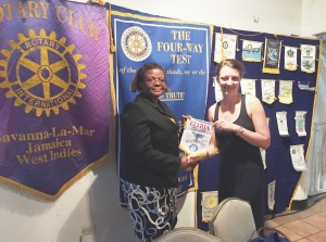 Jillian presenting the Rotary Club of Elyria banner to Savanna-La-Mar President Viviene Richards