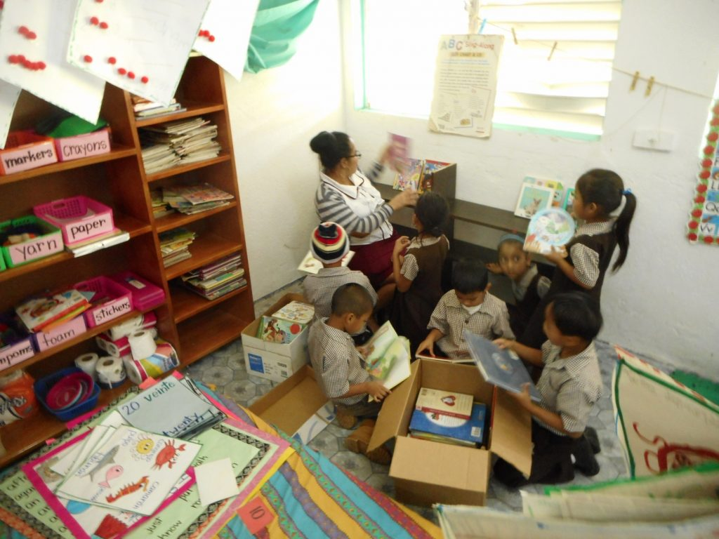 After the shelving is built teachers with the help of the mission team... and in this case students put away the books.